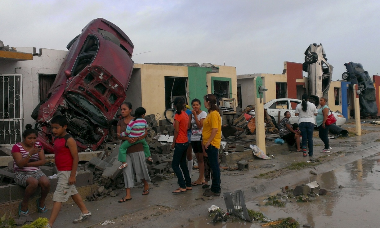 Cars flipped up against houses in Ciudad Acuna after a tornado struck the city. Photograph: Reuters